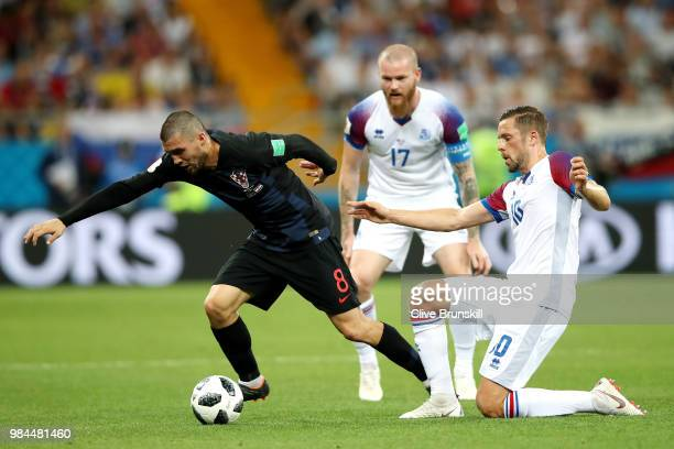 Gylfi Sigurdsson of Iceland tackles Mateo Kovacic of Croatia as Aron Gunnarsson looks on during the 2018 FIFA World Cup Russia group D match between...