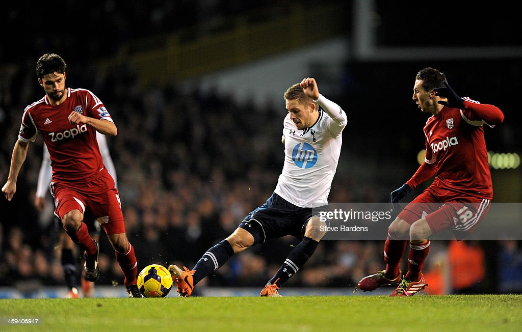 Gylfi Sigurdsson of Spurs takes a shot on goal as Claudio Yacob (L) and Morgan Amalfitano (R) of West Bromwich closes in during the Barclays Premier League match between Tottenham Hotspur and West Bromwich Albion on December 26 2013 in London, England.