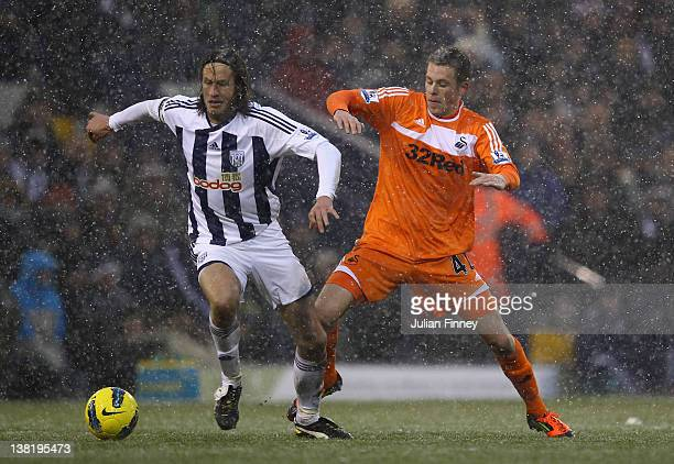 Gylfi Sigurdsson of Swansea battles with Jonas Olsson of West Brom during the Barclays Premier League match between West Bromwich Albion and Swansea...