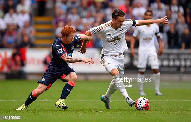 Gylfi Sigurdsson of Swansea City and Jack Colback of Newcastle United compete for the ball during the Barclays Premier League match between Swansea...