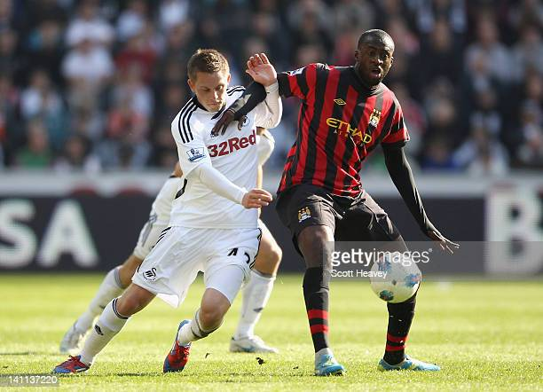 Gylfi Sigurdsson of Swansea City and Yaya Toure of Manchester City battle for the ball during the Barclays Premier League match between Swansea City...