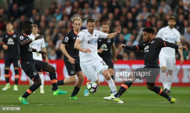 Gylfi Sigurdsson of Swansea City attempts to get past Ashley Williams of Everton and Idrissa Gueye of Everton during the Premier League match between...