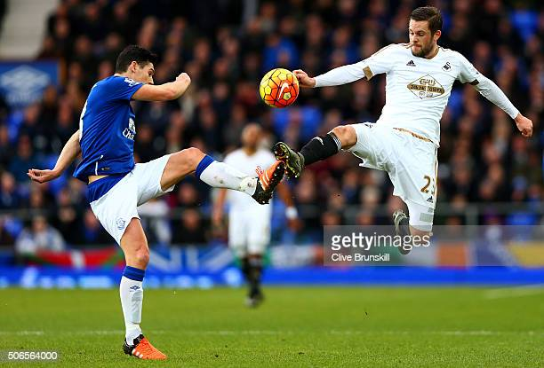 Gylfi Sigurdsson of Swansea City battles for the ball with Gareth Barry of Everton during the Barclays Premier League match between Everton and...
