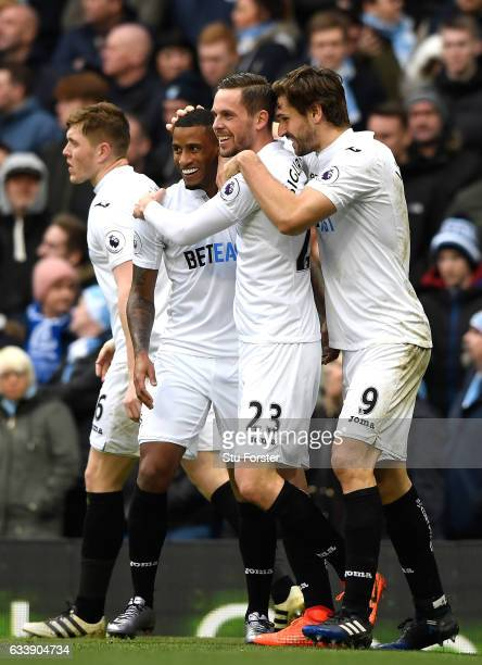 Gylfi Sigurdsson of Swansea City celebrates scoring his sides first goal with team mates during the Premier League match between Manchester City and...