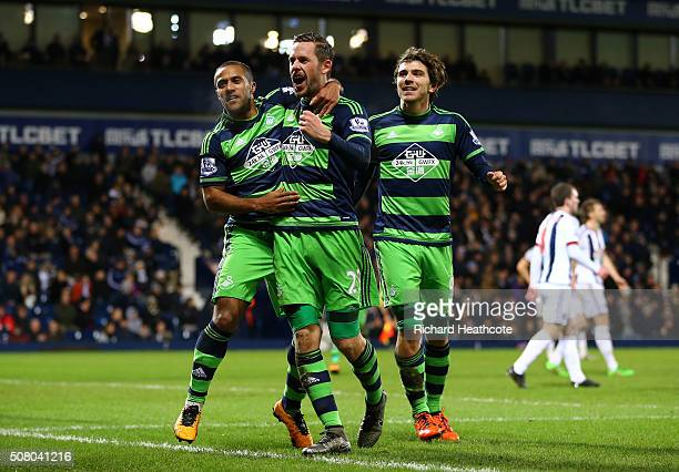 Gylfi Sigurdsson of Swansea City celebrates scoring his team's first goal with his team matesWayne Routledge and Alberto Paloschi during the Barclays...