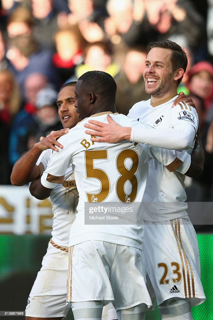 Gylfi Sigurdsson (R) of Swansea City celebrates scoring his team's first goal with his team mates Wayne Routledge (L) and Modou Barrow (C) during the Barclays Premier League match between Swansea City and Norwich City at Liberty Stadium on March 5, 2016 in Swansea, Wales.