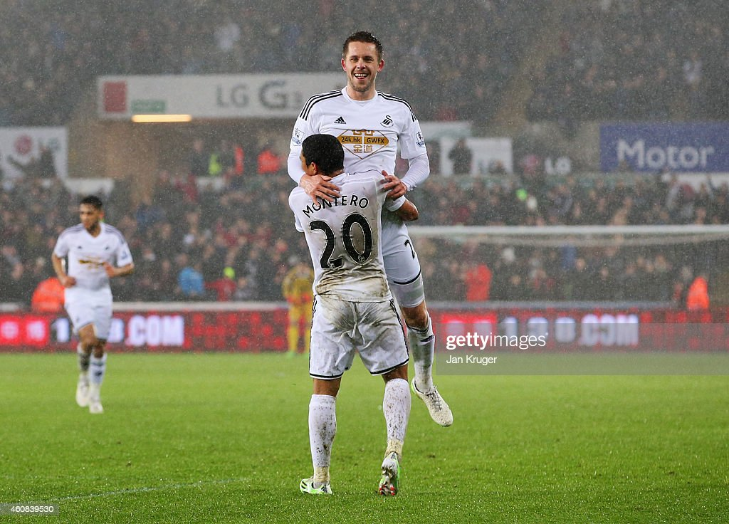 Gylfi Sigurdsson of Swansea City celebrates with Jefferson Montero as he scores their first goal during the Barclays Premier League match between Swansea City and Aston Villa at Liberty Stadium on December 26, 2014 in Swansea, Wales.