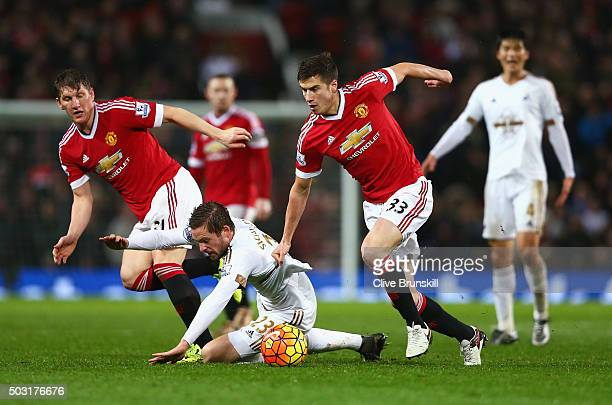 Gylfi Sigurdsson of Swansea City competes for the ball against Bastian Schweinsteiger and Paddy McNair of Manchester United during the Barclays...