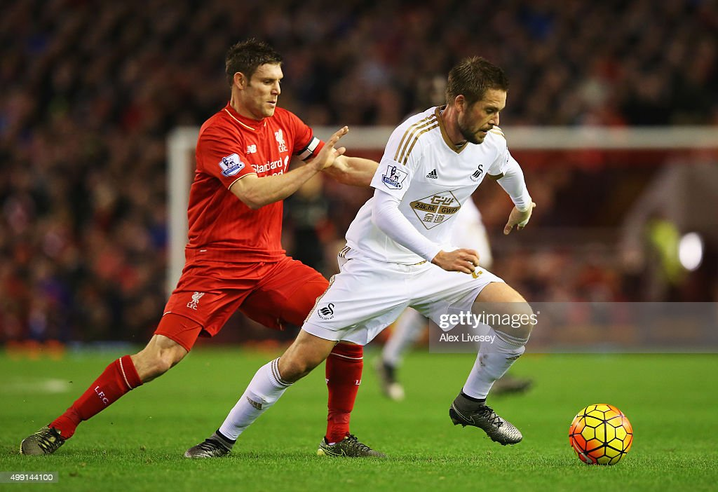 Gylfi Sigurdsson of Swansea City evades James Milner of Liverpool during the Barclays Premier League match between Liverpool and Swansea City at Anfield on November 29, 2015 in Liverpool, England.