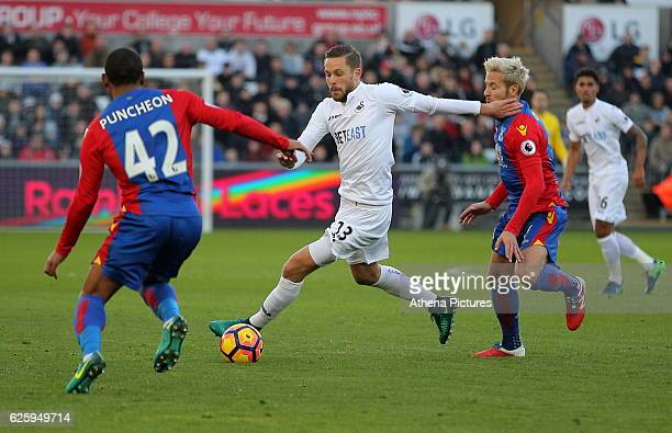 Gylfi Sigurdsson of Swansea City gets past Jason Puncheon and Yohan Cabaye of Crystal Palace during the Premier League match between Swansea City and...