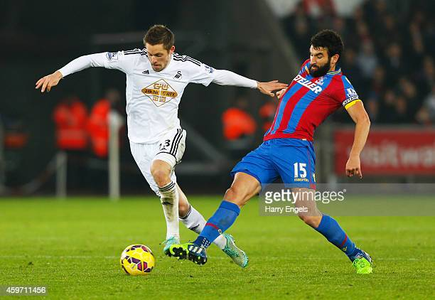 Gylfi Sigurdsson of Swansea City holds off Mile Jedinak of Crystal Palace during the Barclays Premier League match between Swansea City and Crystal...