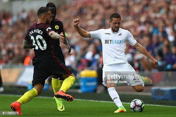Gylfi Sigurdsson of Swansea City is challenged by Nicolas Otamendi of Manchester City during the Premier League match between Swansea City and...