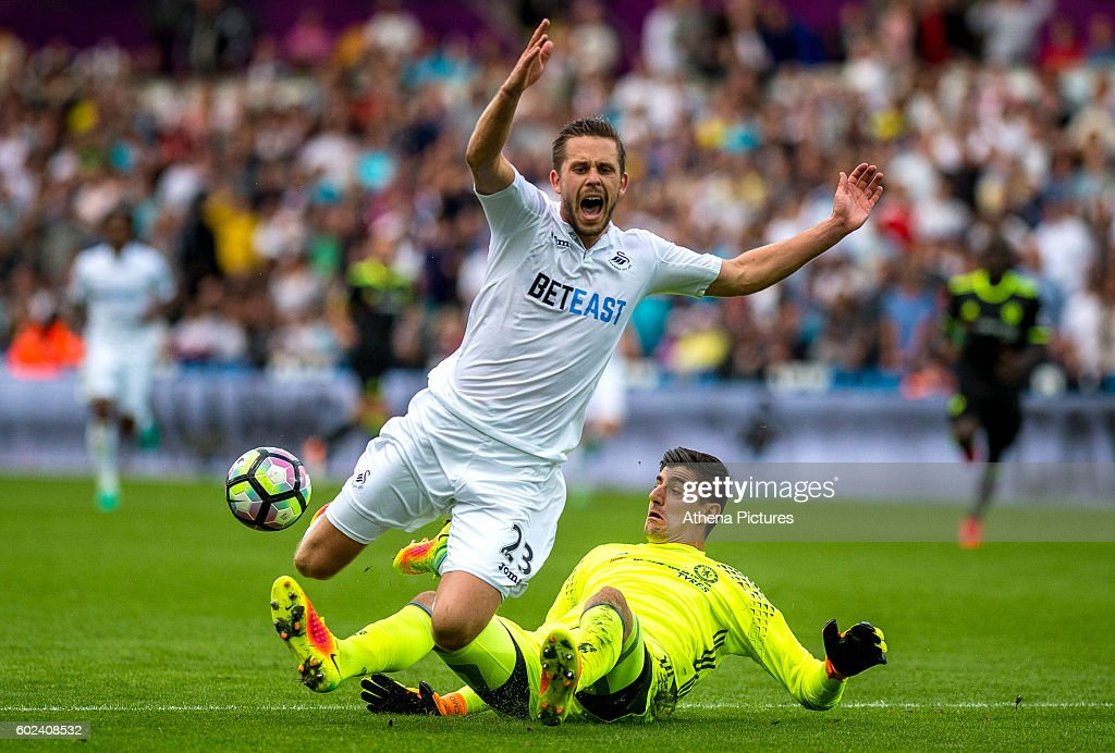 Gylfi Sigurdsson of Swansea City is fouled by Thibaut Courtois of Chelsea leading to a penalty during the Premier League match between Swansea City and Chelsea at The Liberty Stadium on September 11, 2016 in Swansea, Wales.