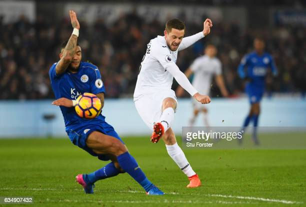 Gylfi Sigurdsson of Swansea City shoots past Danny Simpson of Leicester City during the Premier League match between Swansea City and Leicester City...