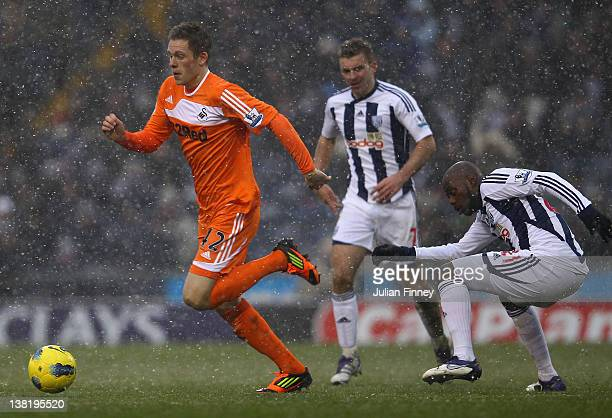 Gylfi Sigurdsson of Swansea moves away from Youssouf Mulumbu of West Brom during the Barclays Premier League match between West Bromwich Albion and...