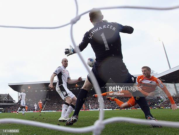 Gylfi Sigurdsson of Swansea shoots past Fulham goalkeeper Mark Schwarzer to score the opening goal of the Barclays Premier League match between...