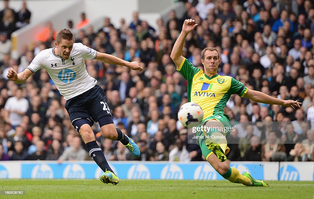 Gylfi Sigurosson of Spurs scores the opening past Steven Whittaker of Norwich City during the Barclays Premier League match between Tottenham Hotspur and Norwich City at White Hart Lane on September 14, 2013 in London, England.