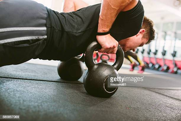 gym athlete doing push-ups on kettlebells