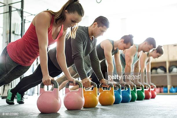 gym class doing push-ups on kettlebells - bodybuilding stockfoto's en -beelden