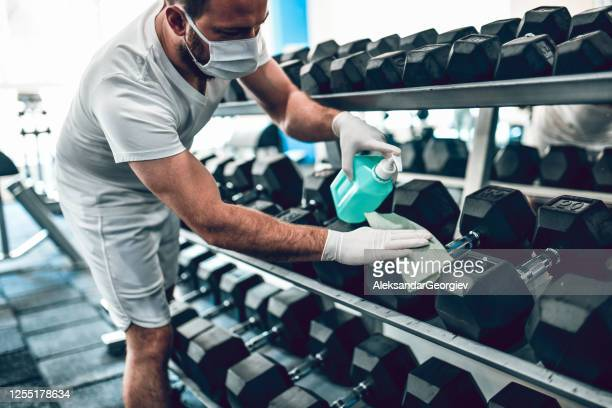 gym disinfection by male with face mask - health club stock pictures, royalty-free photos & images
