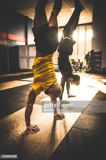 Gym fitness workout: Two man doing a handstand