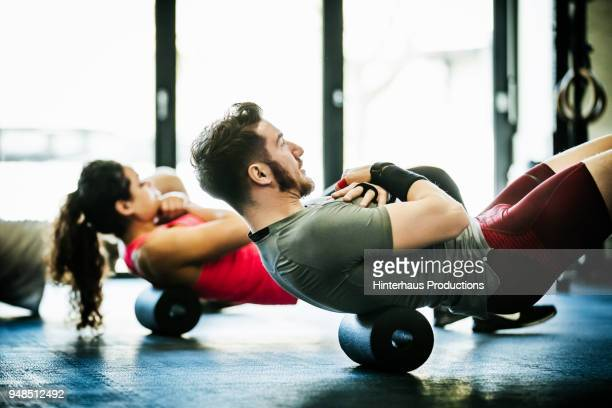 gym goers performing floor exercises together - treino esportivo - fotografias e filmes do acervo