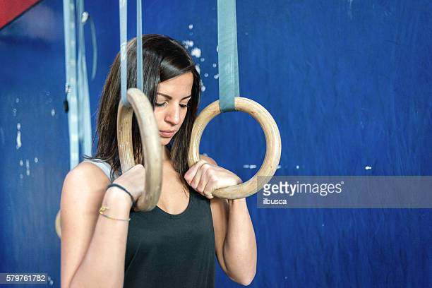 gym gym workout: Woman using rings