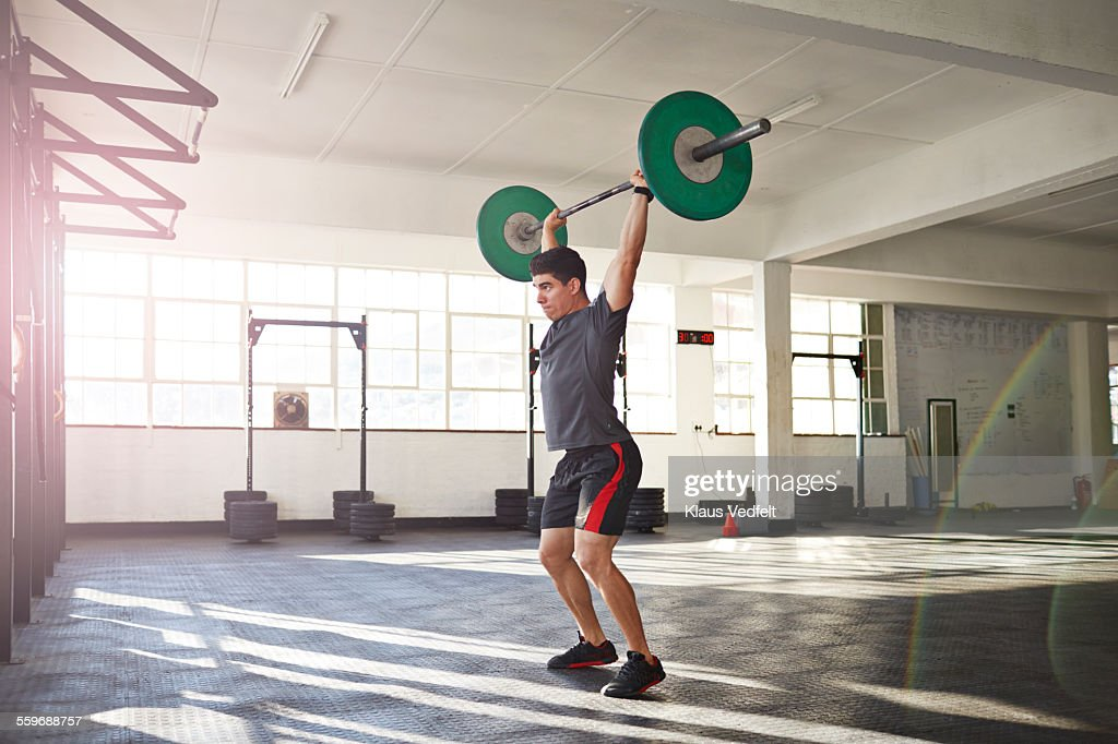 gym instructor lifting barbell at urban gym : Stock Photo