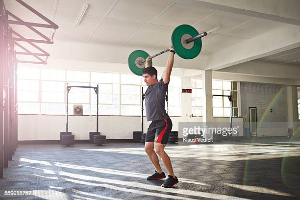 gym instructor lifting barbell at urban gym