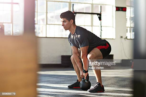 gym instructor lifting kettlebell at urban gy - hurken stockfoto's en -beelden