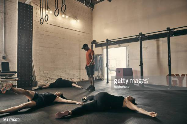gym instructor supervising people doing floor exercises in gym - heshphoto stock pictures, royalty-free photos & images