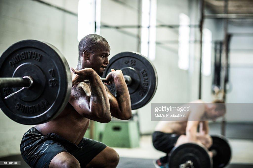 gym - Men doing front squats : Stock Photo