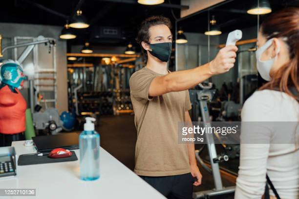 gym owner using infrared thermometer to check customer's body temperature - opening event stock pictures, royalty-free photos & images