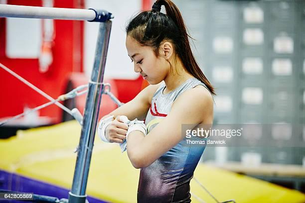 Gymnast adjusting bar grips before bar exercises