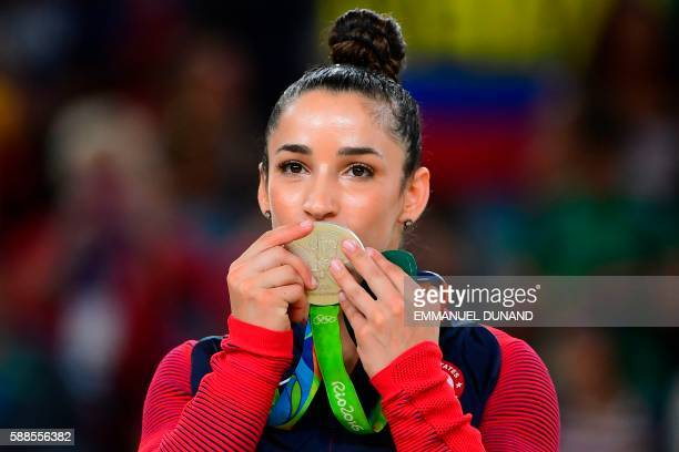US gymnast Alexandra Raisman celebrates with her silver medal on the podium after the women's individual allaround final of the Artistic Gymnastics...