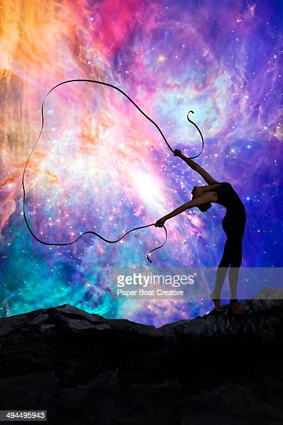 Gymnast dancing with ribbon against cosmic sky