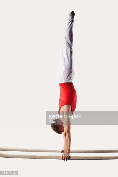 gymnast doing handstand on parallel bars - parallel stock photos and pictures
