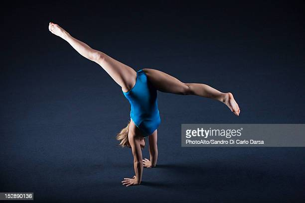 gymnast doing handstand with legs split - gympak stockfoto's en -beelden