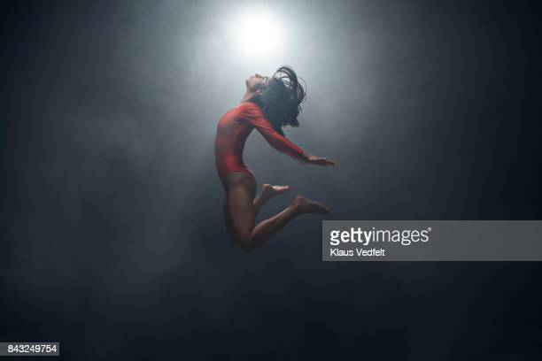 gymnast doing jump in leotard - gymnastics stock pictures, royalty-free photos & images
