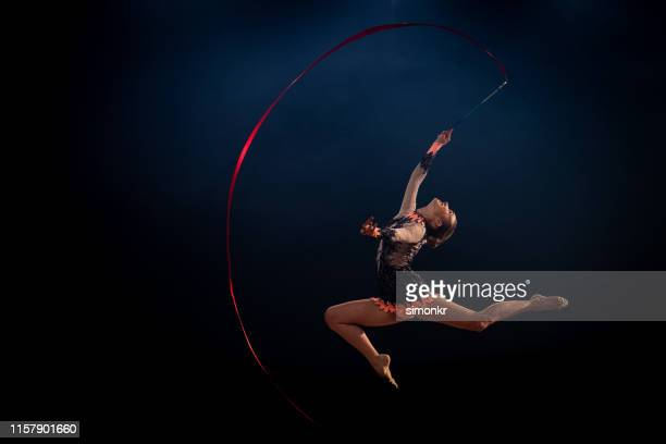 gymnast doing rhythmic gymnastics with red ribbon - rhythmic gymnastics stock pictures, royalty-free photos & images