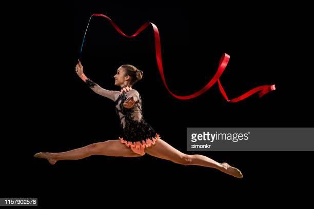 gymnaste faisant la gymnastique rythmique avec le ruban rouge - gymnastique au sol photos et images de collection