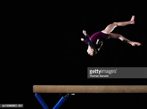 Gymnast (12-13) flipping on balance beam