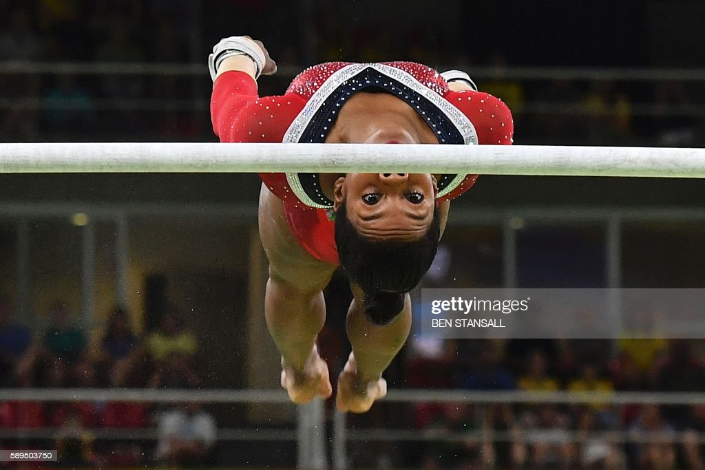 TOPSHOT - US gymnast Gabrielle Douglas competes in the women's uneven bars event final of the Artistic Gymnastics at the Olympic Arena during the Rio 2016 Olympic Games in Rio de Janeiro on August 14, 2016. / AFP / Ben STANSALL