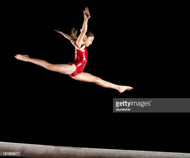 Gymnast girl isolated on black.