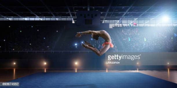 A gymnast girl makes a leap on a large professional stage