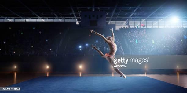 Une fille gymnaste fait un saut sur une grande scène professionnelle