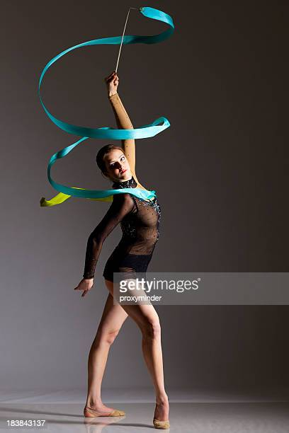 gymnast girl on grey background - rhythmic gymnastics stock pictures, royalty-free photos & images