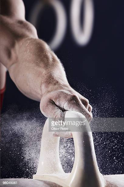 gymnast gripping to a pommel horse