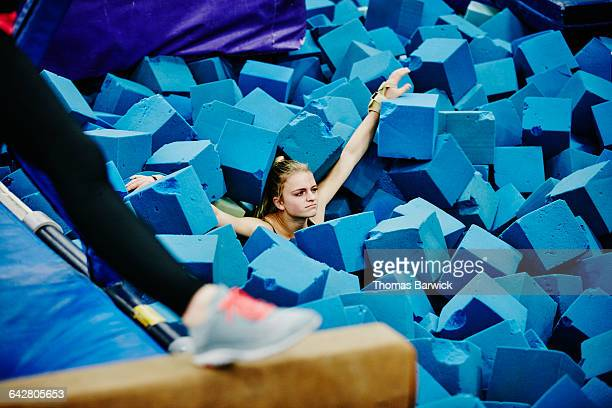 Gymnast in foam pit after dismount off trampoline