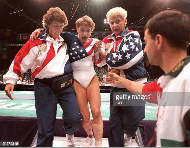 US gymnast Kerri Strug screams in pain as she is carried from the floor by team officials after she injured her ankle during the women's team...